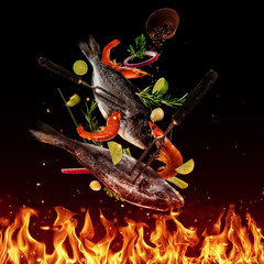 Flying raw sea bream fish above grill flames