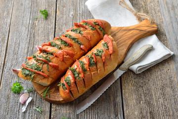 Überbackenes Baguette mit frischer Kräuterbutter und scharfer Chorizo Salami frisch aus dem Ofen serviert – Spanish snack: Baked bread with herb butter and hot Chorizo salami