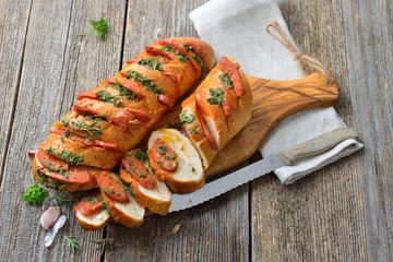 Überbackenes Baguette mit frischer Kräuterbutter und scharfer Chorizo Salami frisch aus dem Ofen serviert – Spanish snack: Baked bread with herb butter and spicy Chorizo salami