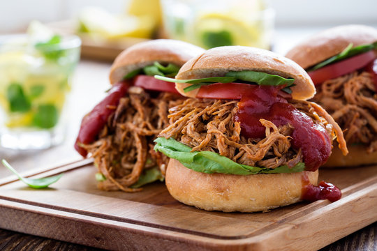 Pulled pork sandwiches with leaf vegetables, tomato and bbq sauce