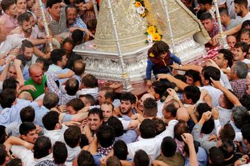 Pilgrims carry the Virgin of El Rocio statue during a procession around the shrine of El Rocio statue in Almonte, southern Spain