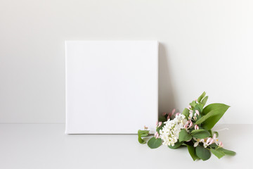 Mock up poster on gray background. White square canvas and romantic bouquet of flowers.