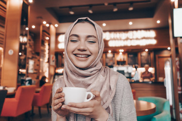 beautiful Muslim girl with a headscarf sitting in an oriental cafe, drinking fragrant coffee and laughing