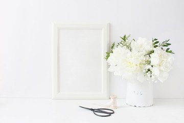 White blank wooden frame mockup. Wedding table still life composition with floral bouquet made of peony and Gypsophila flowers, silk ribbon and vintage scissors on the table. Home decor.
