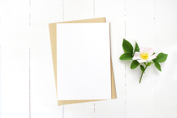 Feminine wedding stationery, floral desktop mock-up scene. Blank greeting card, craft envelope and blooming wild rose branch. Old white wooden table background. Flat lay, top view.