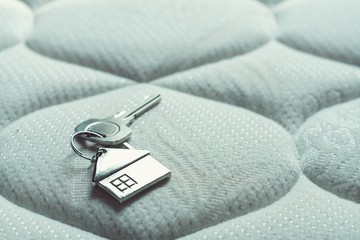 Home key with house keychain on bed, property concept