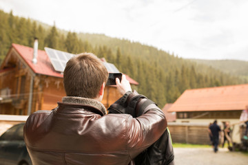 Male tourist taking picture of the Carpathians on mobile phone during his vacation
