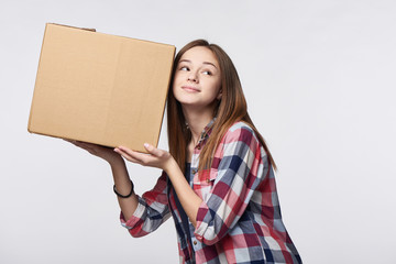 Delivery, relocation and unpacking. Smiling young woman holding cardboard box near her ear listening guessing what is inside, isolated