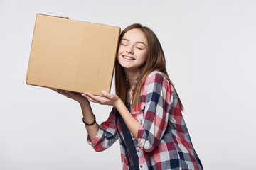 Delivery, relocation and unpacking. Smiling young woman holding cardboard box near her ear listening guessing what is inside with closed eyes, isolated