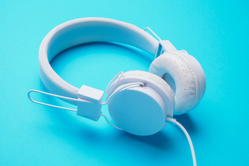 Picture of white headphones on blue background