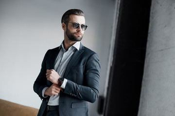 Young bearded stylish businessman leader indoors at office wearing sunglasses walking fixing sleeves with watch looking aside serious
