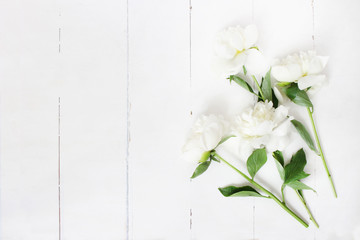 Styled stock photo. Feminine wedding table composition with white peonies flowers on old white wooden background. Empty space. Top view. Picture for blog.