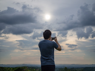 Man taking picture from phone with sunset and evening sky