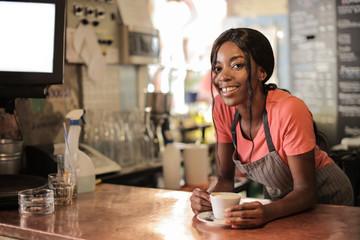 Smiling waitress serving cappuccino