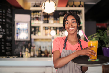 Smiling waitress serving a drink