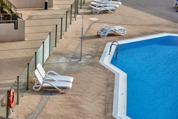 A few empty chaise lounges stand at the luxurious pool, there are no people around. Rest in an expensive and exquisite beautiful hotel in a famous resort. A summer morning by the swimming pool.