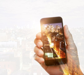 Hand photographing city with smartphone