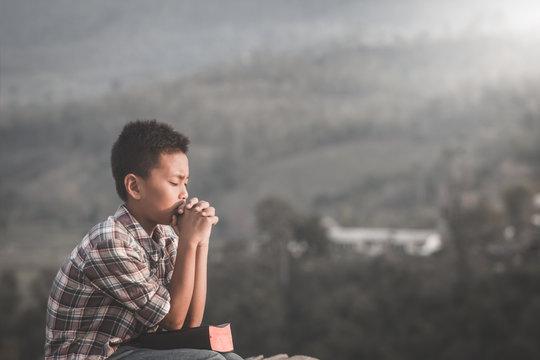 boy praying on holy bible.