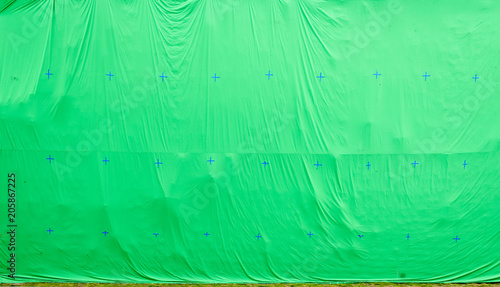 giant green screen chroma key background on commercial set stock