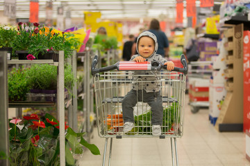 Toddler baby boy, sitting in a shopping cart in grocery store, smiling and eating bread