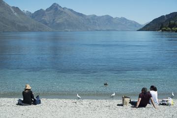 Personas descansando a la orilla de un lago de agua clara y azul frente a un paisaje de montañas Escena diurna, cielo azul y despejado. Nueva Zelanda.