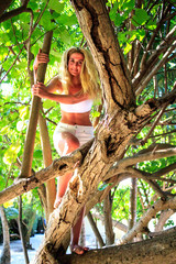 Gorgeous blond woman with long hair on a branch in the forest