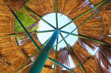 A beach umbrella made of peeled green metal and dry palm leaves from which one can see the sky and a green tree