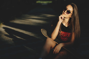 Stunning young caucasian girl with sunglasses sitting in a park with a skate on her shoulders and looking into camera seriously while touching her face with hand.