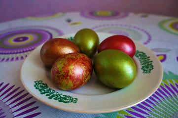 Green and red easter eggs on a white plate with ornament. On the table with lilac and yellow circles.