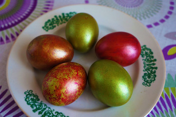 Green and red Easter eggs on a white plate with ornament