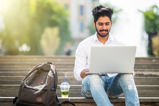 Young handsome indian man sitting on the stairs using laptop in the street in summer day