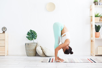 Balance and pacification. Young slender woman doing a yoga exercise - Padangushthasana in a modern home interior. Copyspace