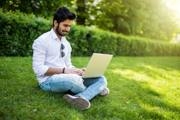 Young indian Student man with a laptop sitting on the grass. Urban style.