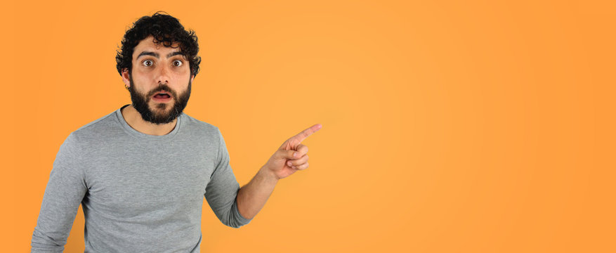 Handsome brunette man with beard and curly hair pointing at copy space. Studio portrait over orange background.