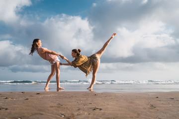 friends doing exercises on beach