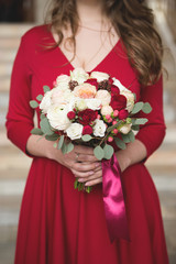 Bride in a red dress. Bridesmaid in a red dress. Wedding bouquet with a red ribbon