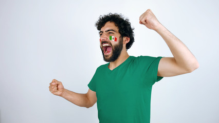 Sport fan screaming for the triumph of his team. Man with the flag of Mexico makeup on his face and green t-shirt.