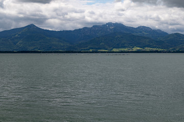 River side of a big lake in front of big mounts in bavaria under grey clouds