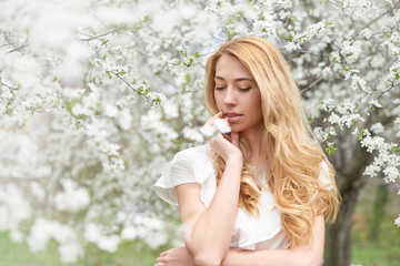 beautiful girl on a background of a blossoming tree in the spring