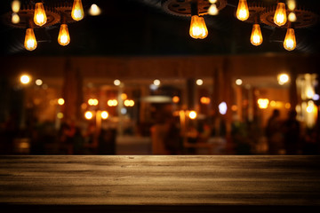 Image of wooden table in front of abstract blurred restaurant lights background.