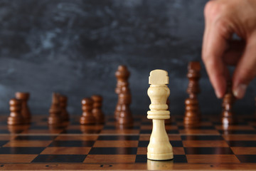 Image of businessman hand moving chess figure over chess board. Business, competition, strategy, leadership and success concept.