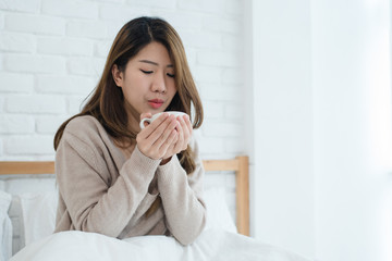 Beautiful Asian woman enjoying warm coffee on bed in her bedroom. Relaxation in bed. Beautiful Asian female wearing comfortable sweater holding a cup of coffee. lifestyle Asian woman at home concept.
