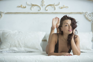 Beautiful natural make-up young girl with curly hair posing in bed in the morning in sexy underwear suit and smiling. Morning Make Up in Boudoir Photography
