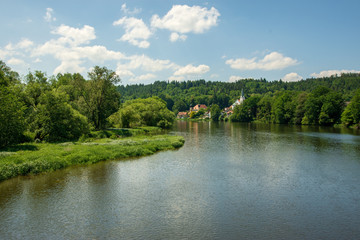 a liitle village with church on a river in bavaria