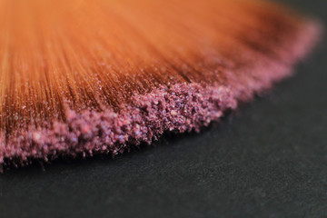 close up. blurred image of a brush smears grains of powder on a black background