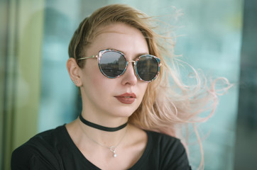 Outdoors portrait of beautiful young woman wearing sunglasses.