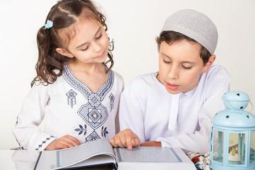 Muslim children reading holy Quran in Ramadan