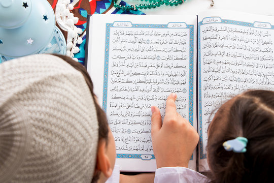 Muslim brother and sister pointing to the word : Ramadan (The holy Month) while reading the Quran in a mosque
