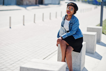 Stylish african american model in glasses hat, jeans jacket and black skirt posed outdoor.