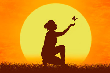 Silhouette of a girl with butterfly flying from her hands against the setting sun.